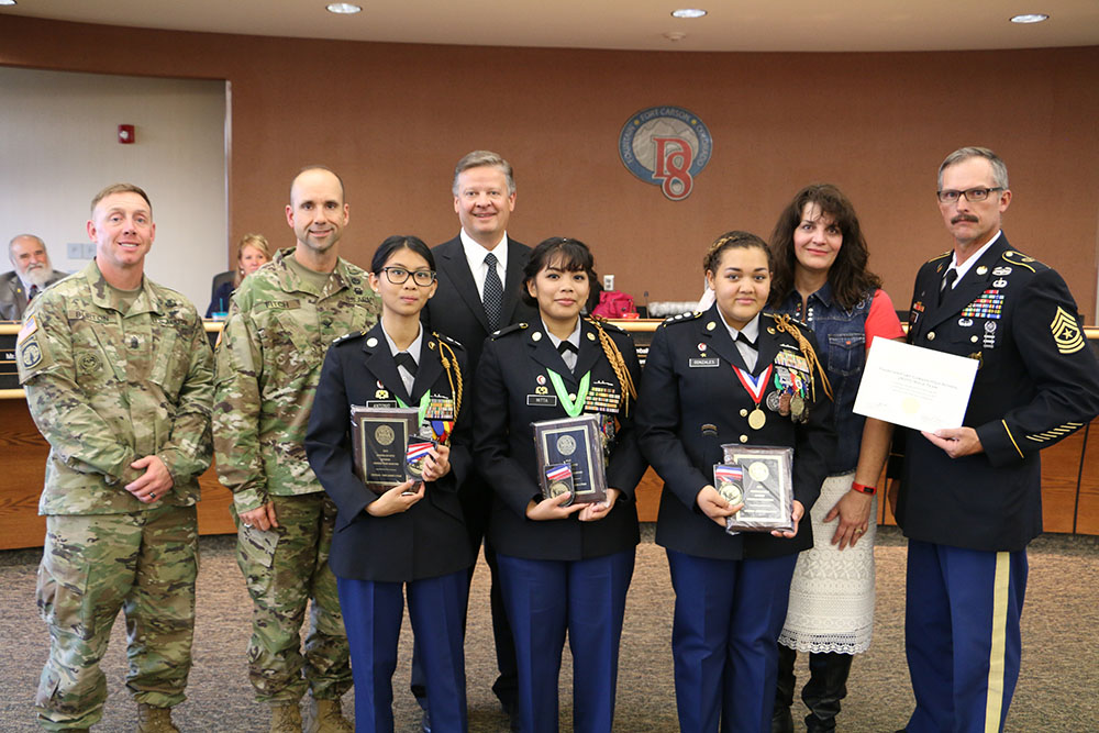 Representatives from the district, school board, and Fort Carson congratulate the JROTC team at a recent school board meeting.