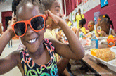 Young girl with sunglasses on eating lunch in cafeteria to represent summer food service program