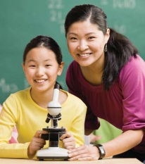 Photo of teacher and student behind a microscope
