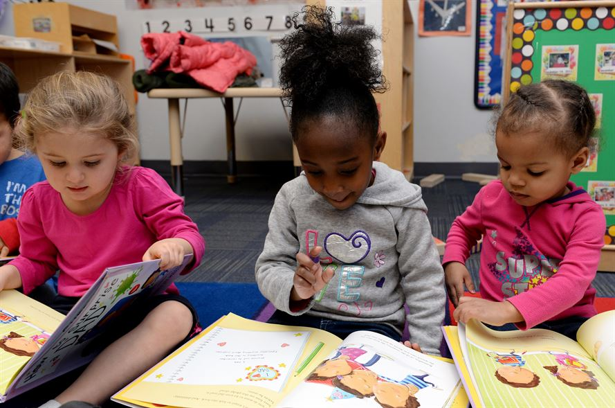 Diverse groups of preschool girls sitting around reading books.