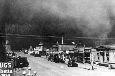A dust storm engulfs the town of Burlington, Colorado (Kit Carson County). Cars are parked on unpaved Main Street in front of the town's commercial storefronts. A grain elevator is at the end of the street.