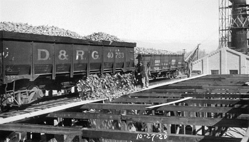 Men watch beets pour from a D.& R.G. railroad freight car