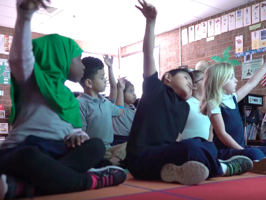 Young students sitting on the floor in a classroom and raising their hands to participate