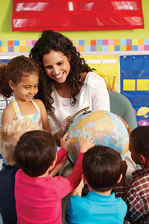 Stock photo of teacher showing globe to elementary students