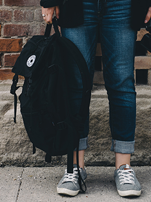 Stock photo of backpack and student's shoes to represent Homeless Youth Awareness Month