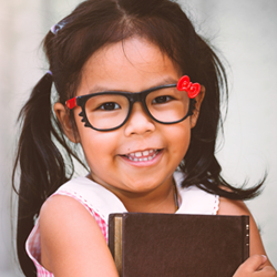 Stock photo of young girl with glasses holding book to represent the READ Act toolkit resources webpage