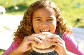 Girl eating sandwich to represent Summer Meals Program call for partners