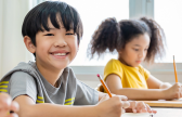 Photo of child at desk smiling to represent state-level assessment results release for Spring 2021