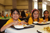 Image of two girls smile while eating lunch in the cafeteria - Link to freed and reduced price meal income guidelines