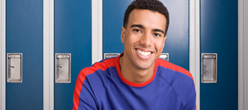 Young man smiling in front of lockers at school