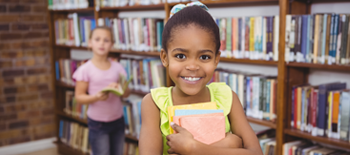 Young girl smiling while holding a book in front of books stacks in library