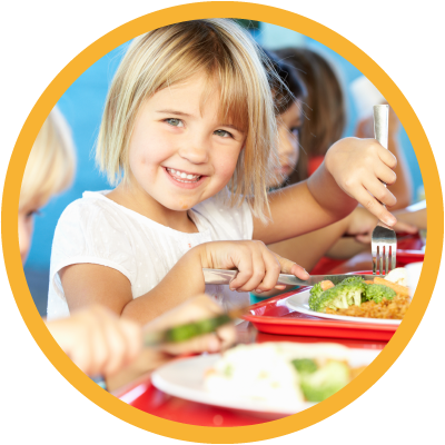 Young child smiling and eating lunch