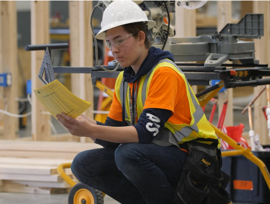 Student in a hard hat reading a manual near heavy equipment