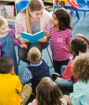 Photo of teacher reading to children in classroom