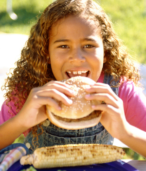 Photo of young girl biting into sandwich to represent summer food service program'd free meals